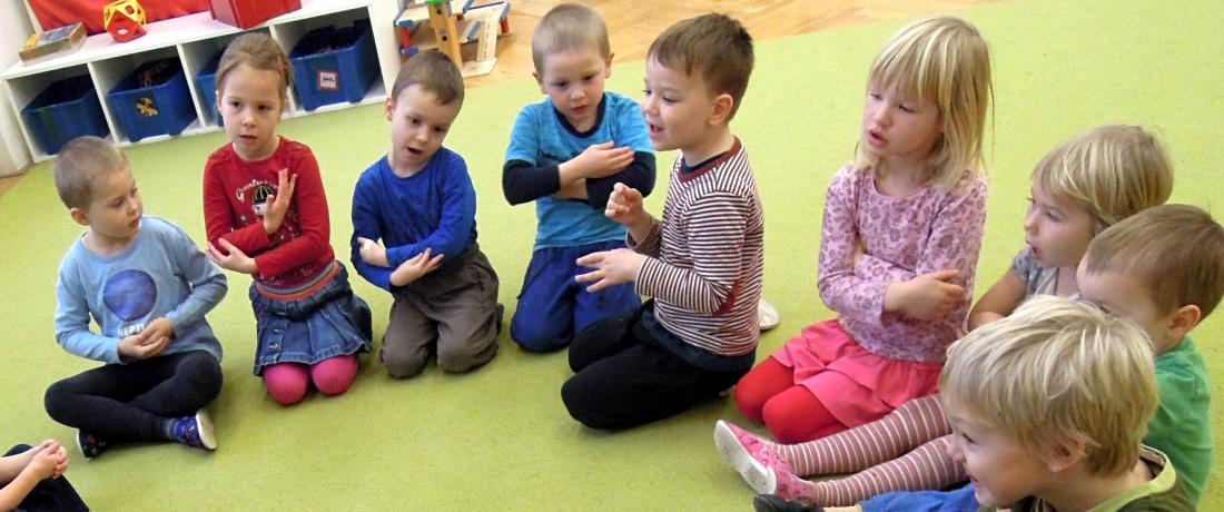 Děti sedí v krožku a chovají pomyslné miminko