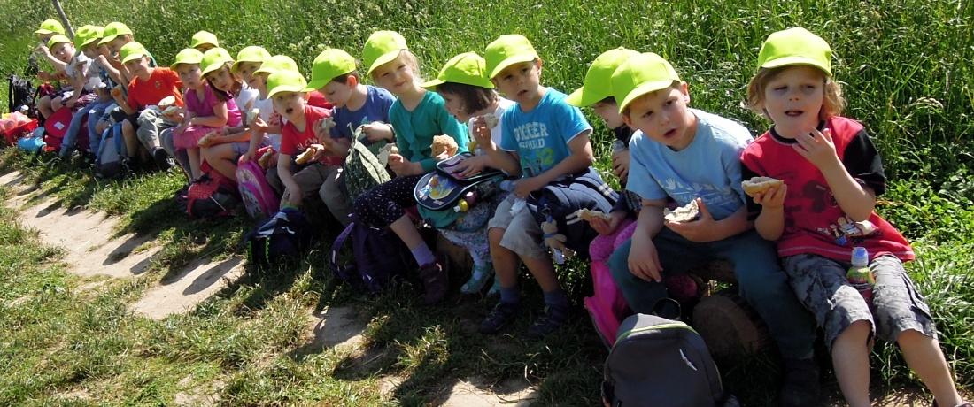 Děti sedí v řadě podél cesty