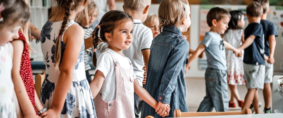 Holčička se drží za ruce ostatních dětí
